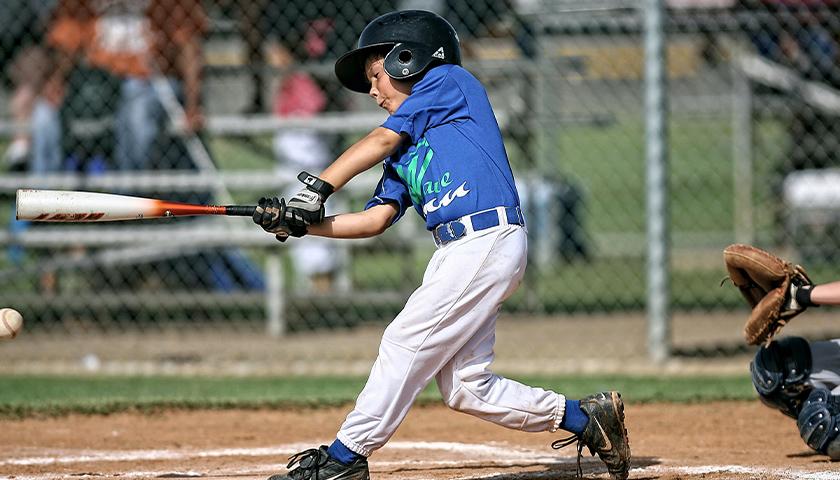 Young boy hitting a baseball