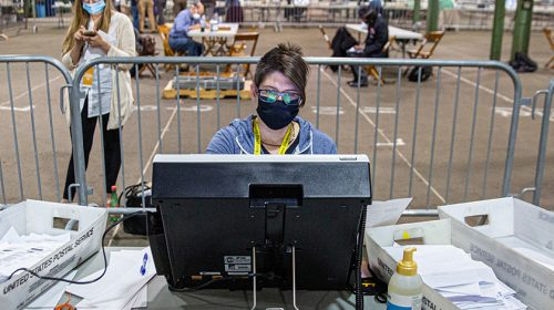 Person with mask on at a computer.