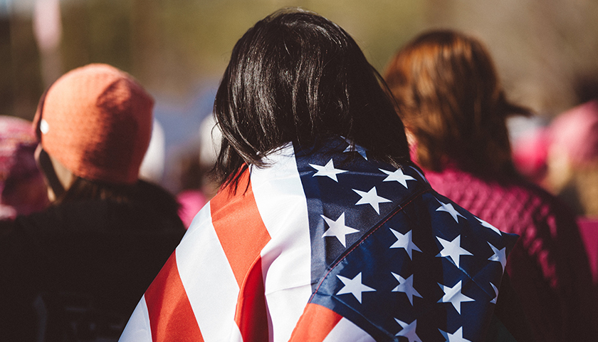 Crowd with woman covered by the American Flag