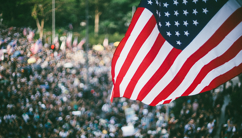 American flag flying above a large crowd.