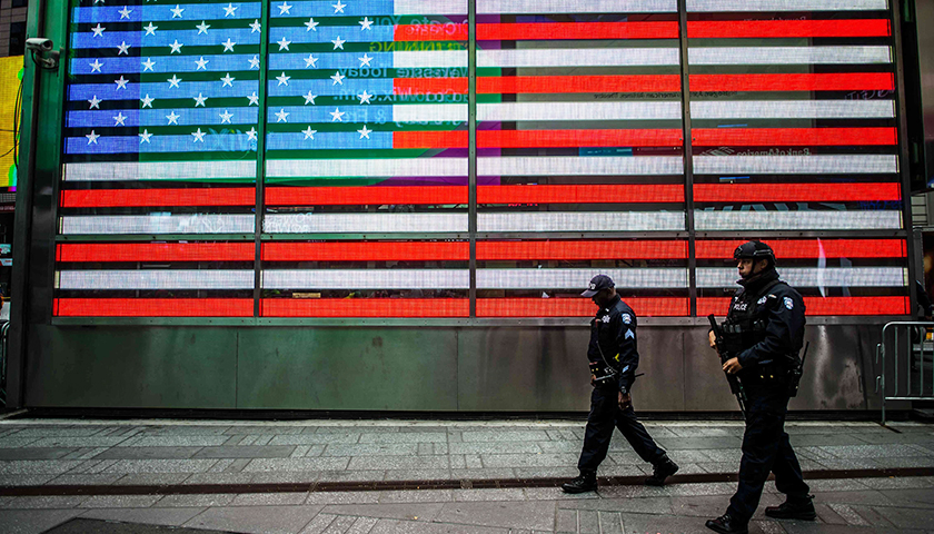 Two police officers walking in front of LED American flag