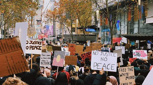 """Group protesting; """"no justice no peace"""" sign"""