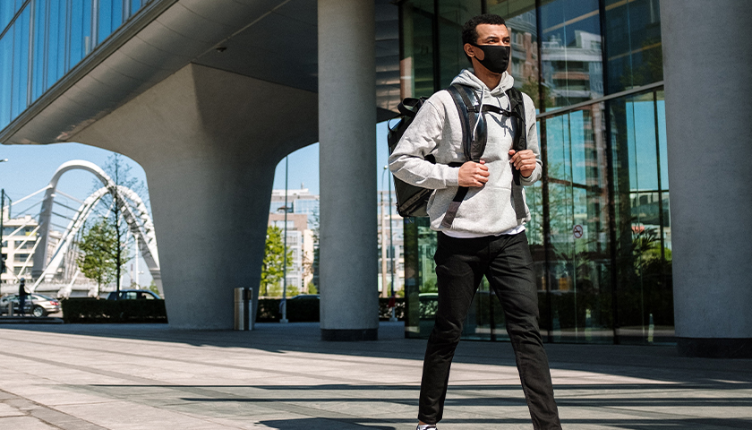 College student walking on campus, wearing mask