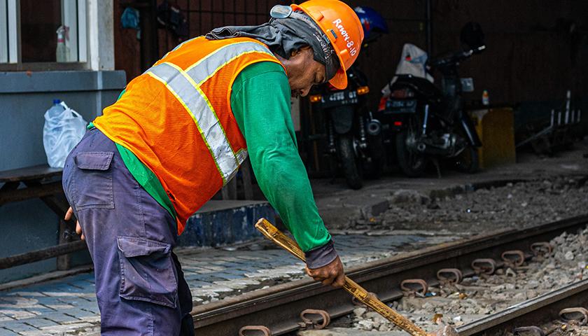 Worker using a sledgehammer on railroad