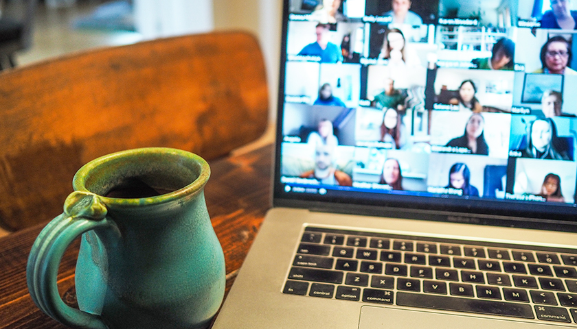 Computer with video chat on screen and mug next to laptop