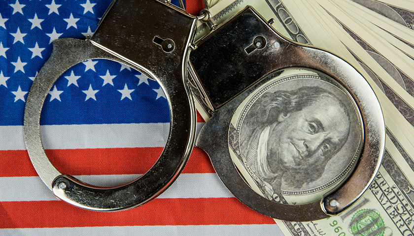 American flag with handcuffs and $100 bills