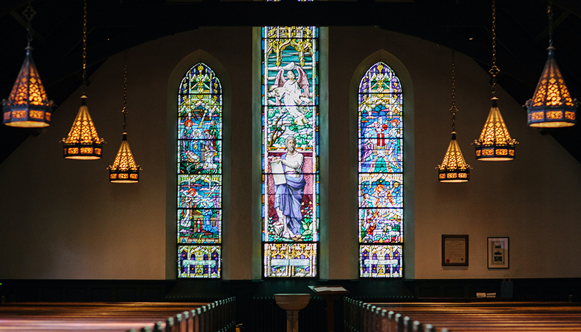 Inside of a church with stained glass and low lighting