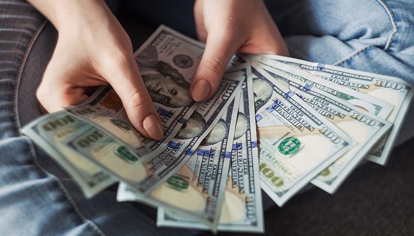 Woman with $100 bills spread open in hands