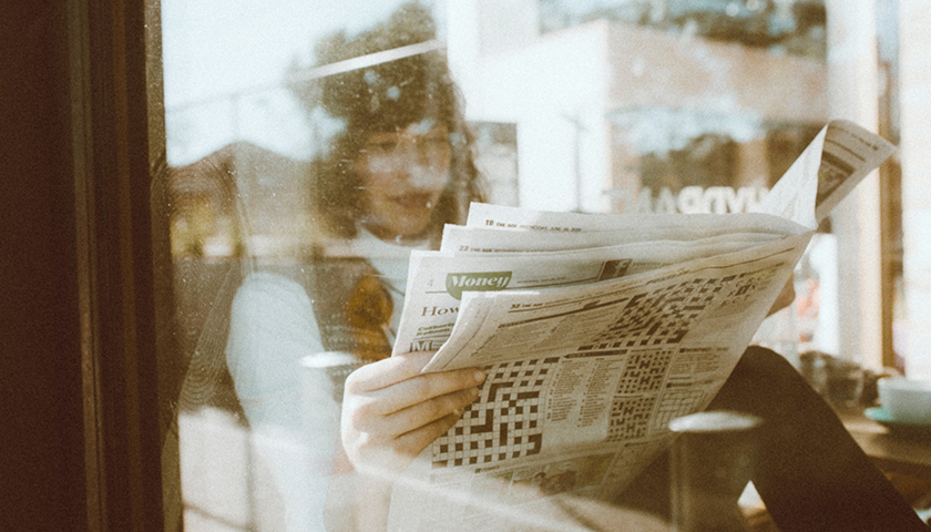 Person holding newspaper inside of cafe