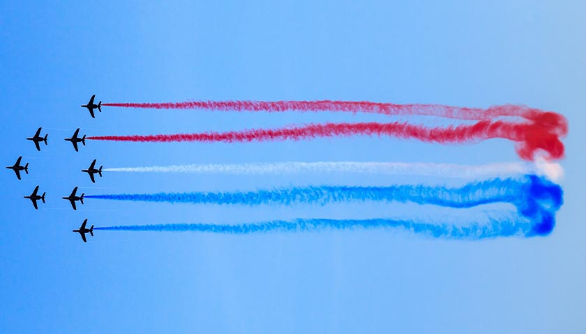 Planes in the sky letting off red, white and blue smoke