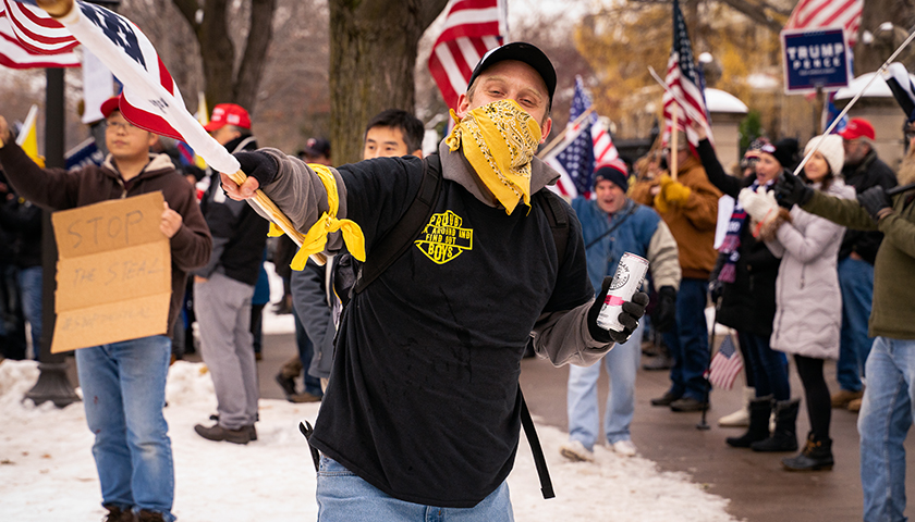 """A member of the """"Proud Boys"""" waves a flag at a """"Stop The Steal"""" rally outside the Minnesota Governor's mansion on November 14th, 2020."""