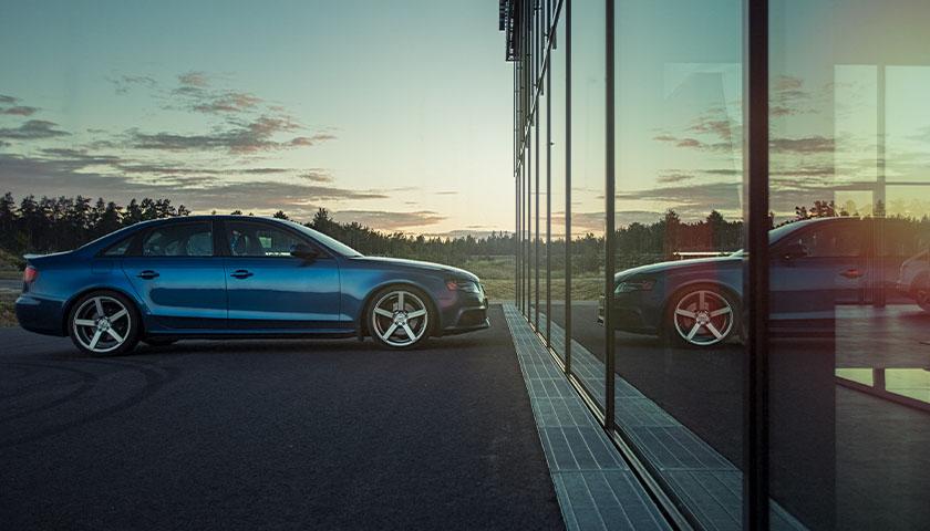 Blue sedan during sunset at dealership in lot
