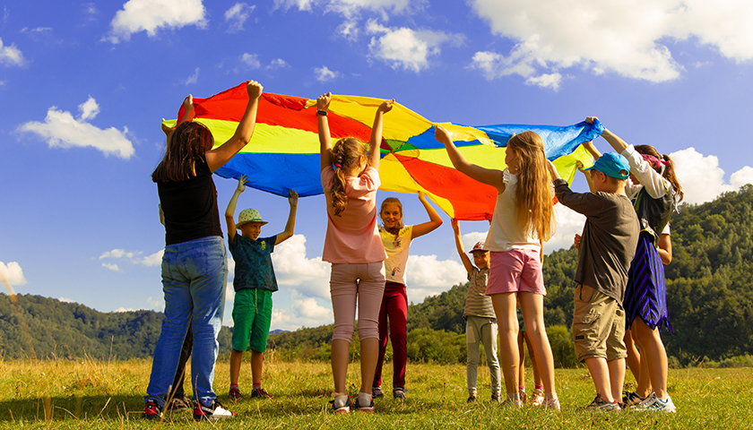 Group of kids playing with a rainbow parachute cloth in a field