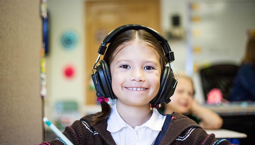 Young girl wearing black headphones, smiling