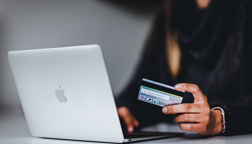 Woman holding credit card, laptop open in front of her